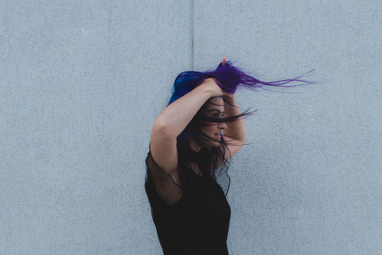 Smiling woman with dyed hair standing against wall