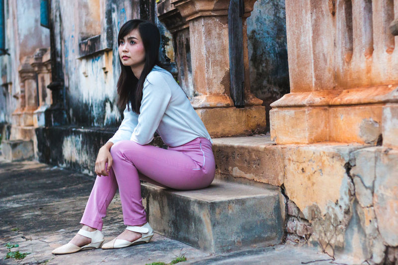 Beautiful young woman sitting at doorway of house