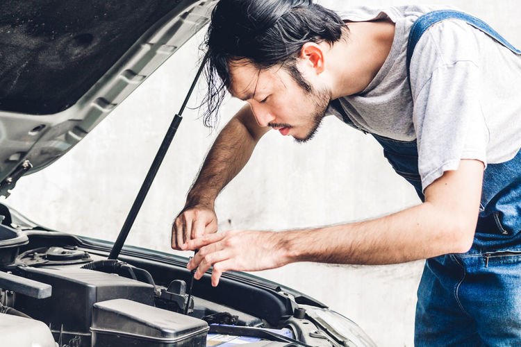 Professional car mechanic in uniform fixing a car engine and repairing checking under the car hood in auto service Casual Clothing Real People Land Vehicle Three Quarter Length Transportation Mode Of Transportation Car One Person Men Motor Vehicle Lifestyles Standing Day Young Adult Young Men Leisure Activity Males  Focus On Foreground Outdoors Jeans Mechanic
