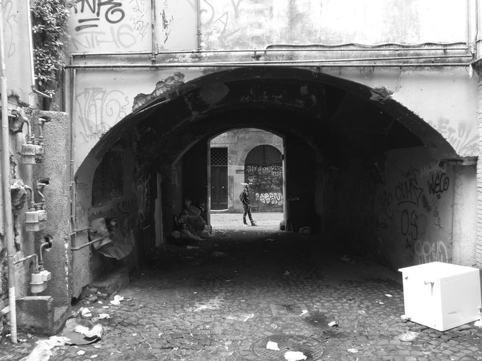 Man standing at entrance of old building