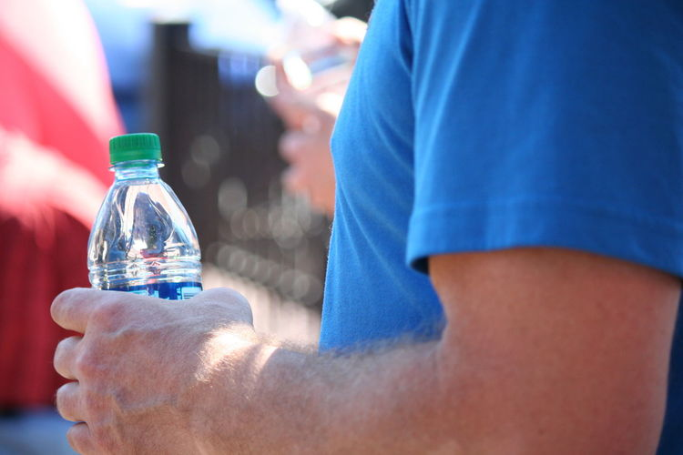 Artesian Well Blue Bottled Water Casual Clothing Close-up Cropped Day Focus On Foreground Leisure Activity Lifestyles Midsection Multi Colored Part Of Selective Focus Unrecognizable Person Water Ceremony Colour Of Life