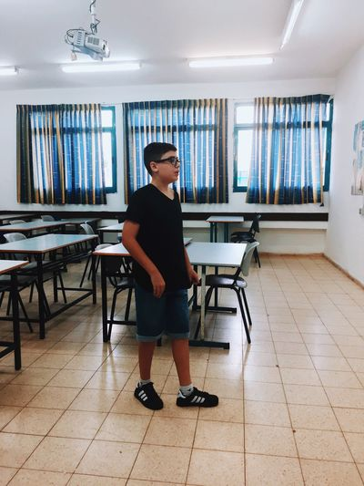Full Length Side View Of Boy Standing In Classroom