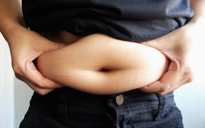 Midsection of overweight woman holding stomach fats while standing against wall