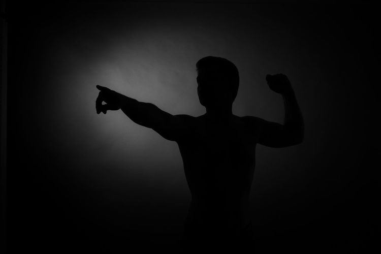 Silhouette of man with arms raised