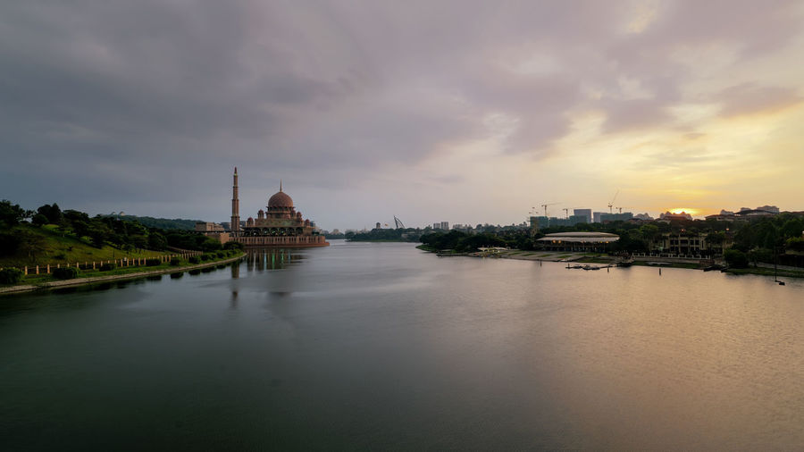 View of mosque at riverbank against cloudy sky