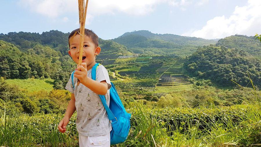 Portrait of boy holding stick on field