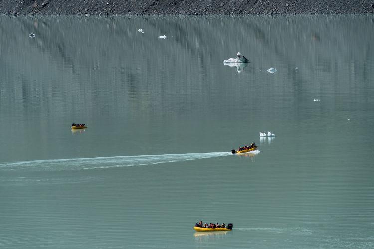 High angle view of people sailing boat in lake at tasman glacier