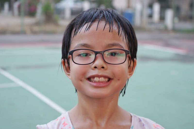 Closeup portrait on sweated face with eyeglasses of Asian girl after exercising. Smiling face of young girl looks at the camera with blurred tennis court in background Sweated Exercise Sport Healthy Lifestyle Portrait Portrait Headshot Glasses Smiling One Person Eyeglasses  Looking At Camera Real People Child Happiness Childhood Lifestyles Day Women Females