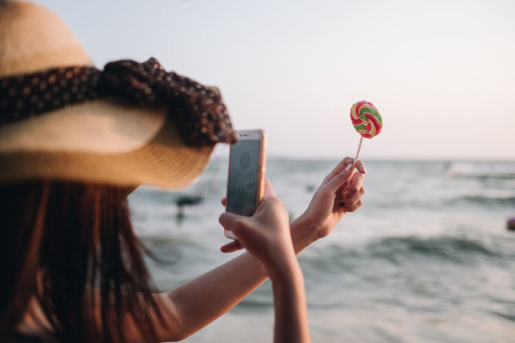 Close-up of woman photographing lollipop at beach against sky