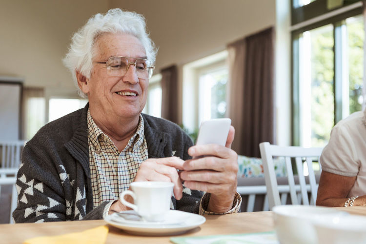 Mid adult man using laptop in coffee cup