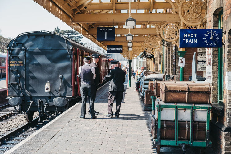 People walking on railroad track in city
