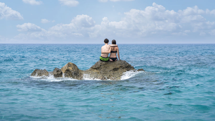 Cloudscape Couple Hug Man Rock Sitting Swimming Woman Bathers Cliff Journey Leisure Nature Ocean Outdoors Real People Relax Scenics Sea Shirtless Sport Togetherness Two People Vacation Water