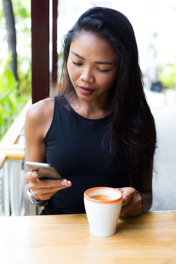 Young Woman With Coffee Cup Using Phone At Table In Cafe