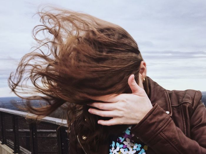 Close-up of woman with brown tousled hair against sky