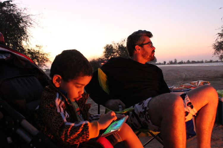 Father and son relaxing at campsite during sunset