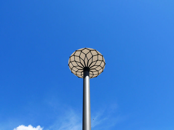 Nature Flower Sky Blue Electric Light Day Outdoors Illuminated Street Light Clear Sky Pole Close-up Beauty In Nature Floodlight No People Hidden Gems  Minimalist Photography  Copy Space Colour Of Life Low Angle View Lighting Equipment Tall - High High Section Spīķeri Break The Mold The City Light AI Now The Graphic City Colour Your Horizn Visual Creativity Capture Tomorrow The Art Of Street Photography