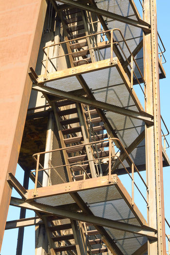 stairway Stairway Architecture Building Building Exterior Built Structure Construction Industry Day Fire Escape Industry Ladder Low Angle View Metal Nature No People Outdoors Railing Sky Staircase Sunlight Window Wood - Material