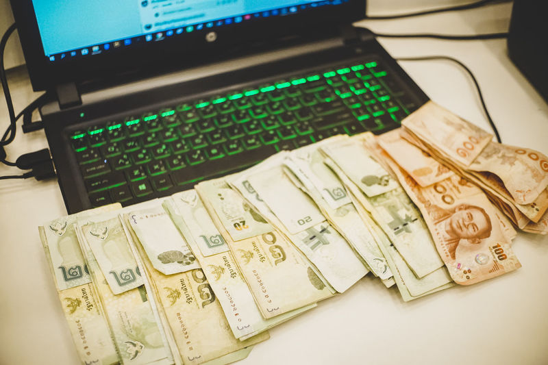 make money with laptop. Light Past Time Thai Thailand Working Business Cash Close-up Communication Computer Computer Equipment Computer Keyboard Connection Currency Finance Focus On Foreground Green Color High Angle View Indoors  Job Keyboard Keyboard Light Laptop Laptop Keyboard Make Money Money No People Number Ocupation Paper Currency Part Time Job Stack Table Technology Text Wealth