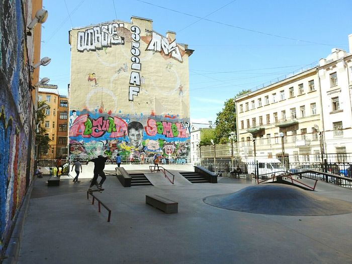 People at skateboard park against graffiti wall in city