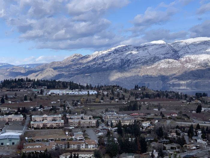 Aerial view of town by mountains against sky
