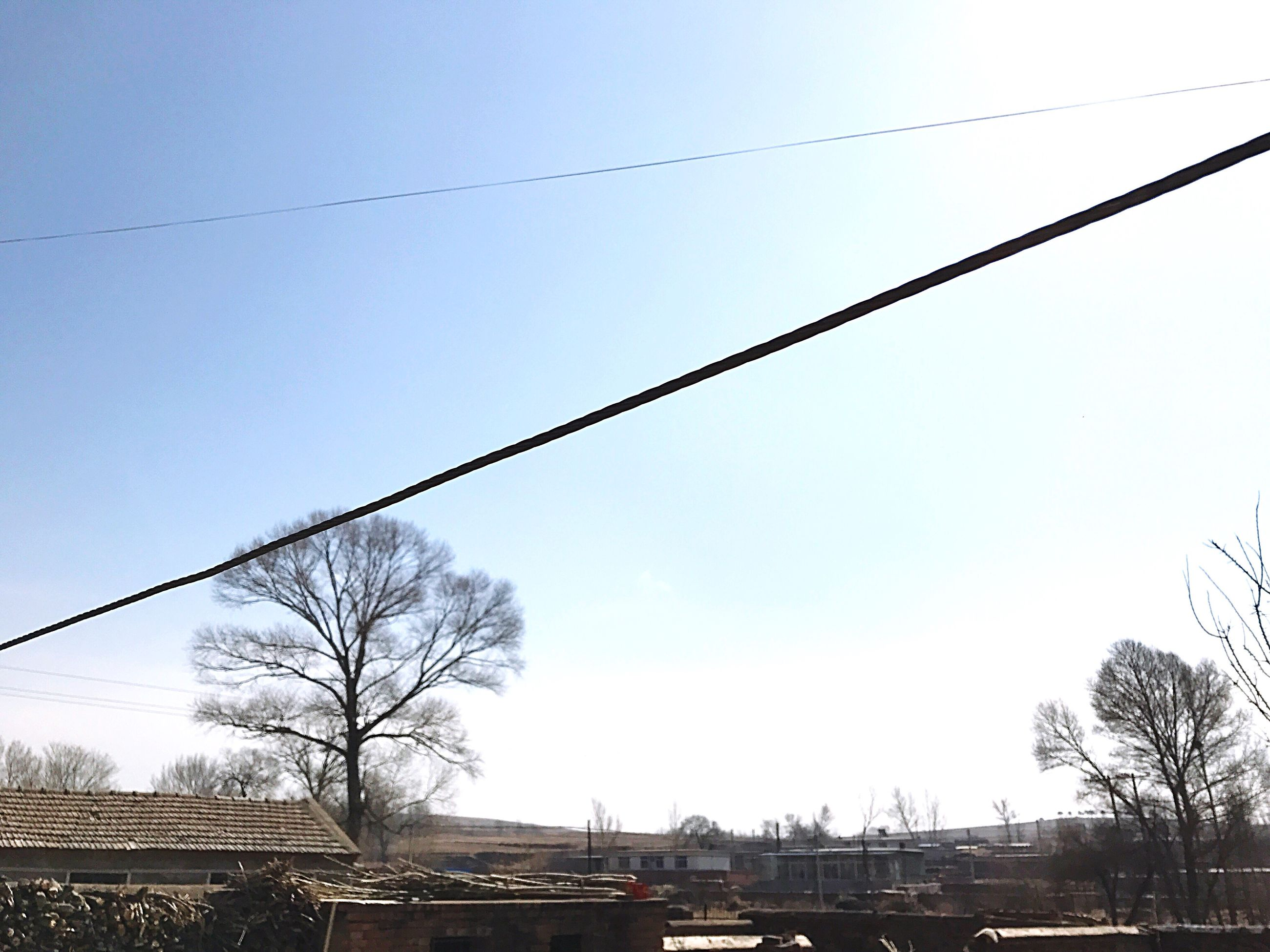 low angle view, sky, outdoors, no people, built structure, transportation, power line, architecture, building exterior, connection, day, tree