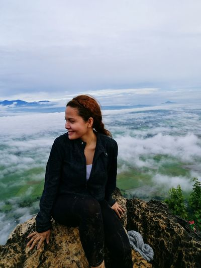 Smiling woman sitting on rock at mountain over clouds against sky