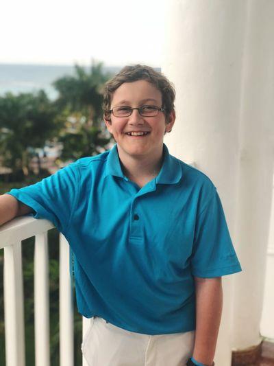 Portrait of smiling boy standing in balcony