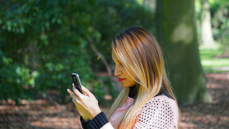 Close-Up Of Woman Using Phone At Park In Sunny Day