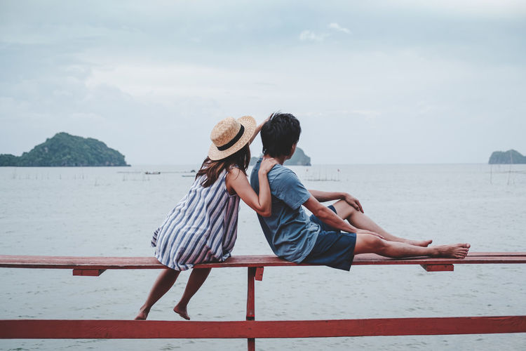 Rear view of couple sitting on railing by sea against sky