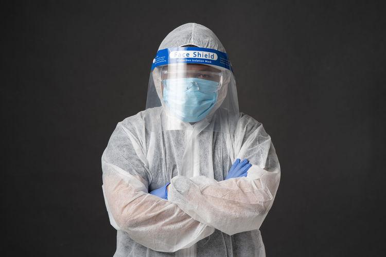 Portrait of doctor wearing mask against black background