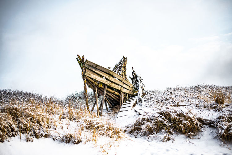 Abandoned structure on snow covered field against sky