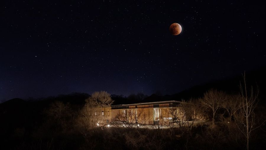 Low Angle View Of Moon Over Illuminated Building At Night