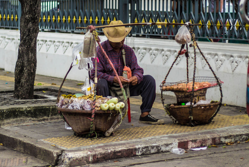 Thailand Street Merchant Peddling His Wares Using a Shoulder Pole Bangkok Food And Drink Merchant Thailand Thailand Street Foods Thailand Street Photography Adult Clothing Container Day Food Food And Drink Front View Hat Healthy Eating Holding Occupation Outdoors Peddling Preparation  Real People Sitting Vegetable Working