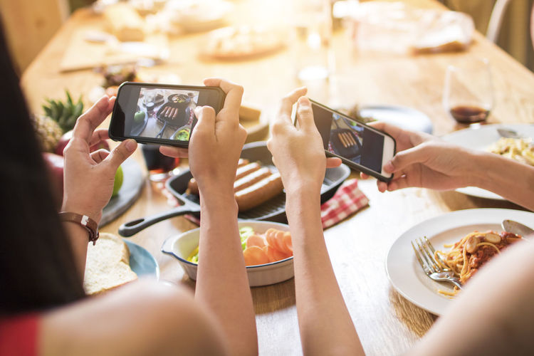 Cropped hands of women photographing food in restaurant