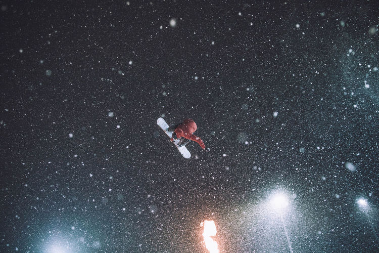 Low angle view of man snowboarding against sky during winter