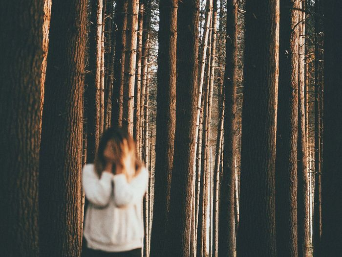 Sad Woman Standing Against Trees In Forest