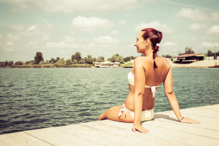 Carefree woman in bikini sitting on a pier and enjoying in summer day at the beach.