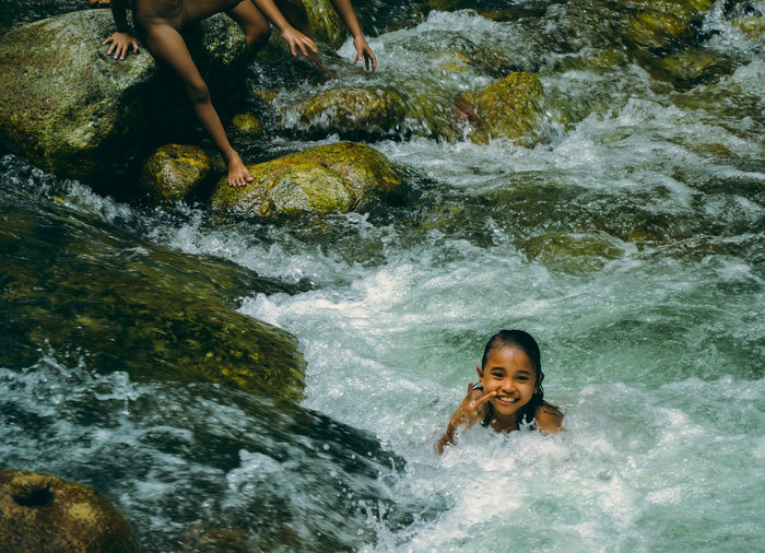 Portrait of girl showing victory sign at geruntum falls