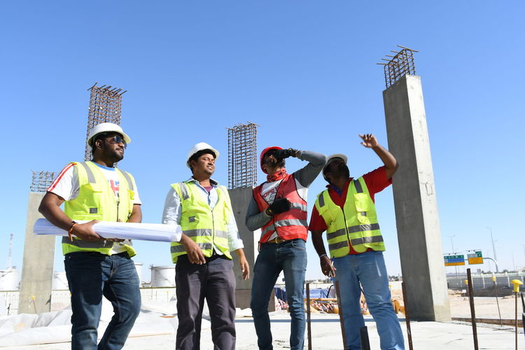 Low Angle View Of Architects Standing At Construction Site Against Clear Blue Sky