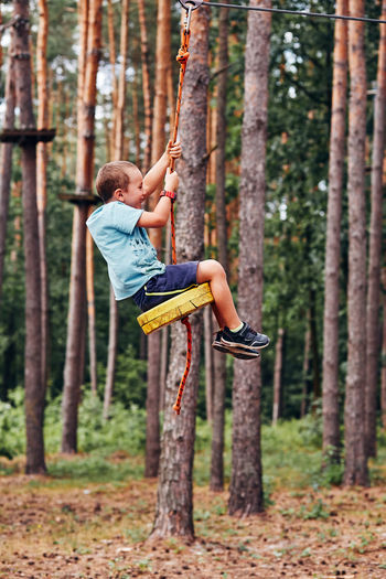 Boy sitting on rope swing in park