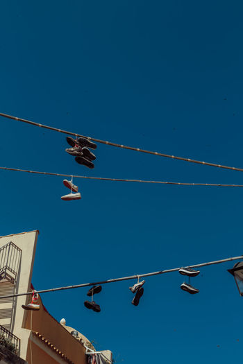 Blue Blue Sky Cable Clear Sky Day Flying Hanging Around Italy Low Angle View Nature No People Outdoors Shoes Sky Summer Transportation Travel Destinations Vapor Trail