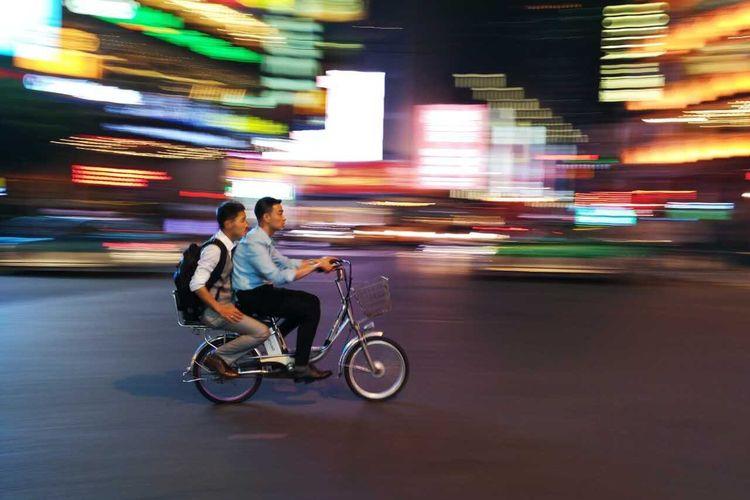 Man riding bicycle on street at night
