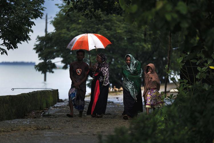 Women standing by wet tree during rainy season