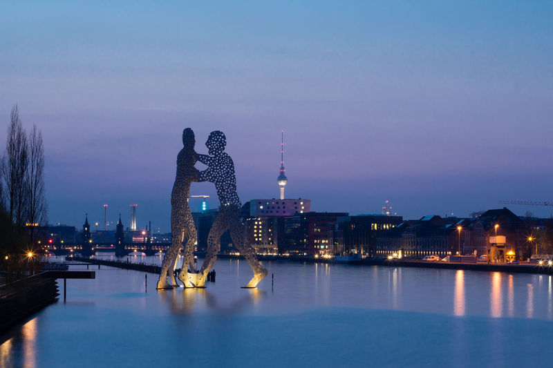 Molecule men sculpture on river in city against sky at night
