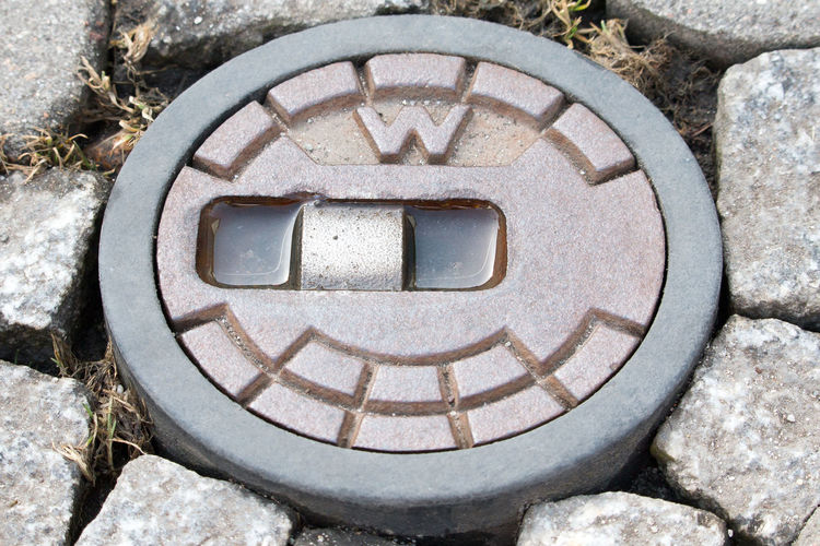 Round street cap for gate valve of a water pipe Close-up Day High Angle View Manhole  Nature No People Outdoors Pebble Rock - Object Sewage Stone - Object Street Cap