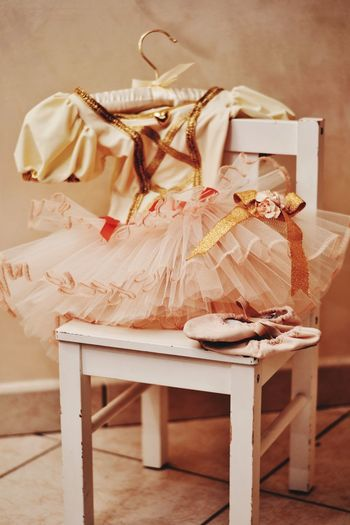 Close-up of dress with ballet shoes on chair