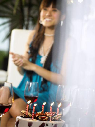Smiling woman sitting by red wineglasses and lit candles on cake in party
