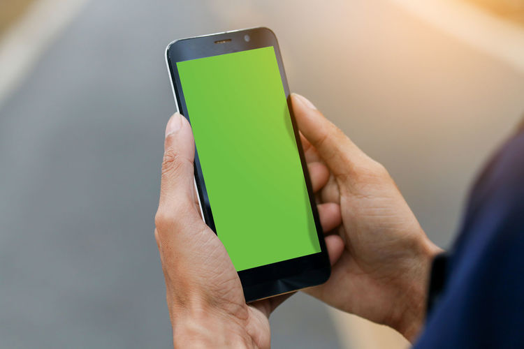 Hand holding smartphone with green screen. Wireless Technology Human Hand Communication Technology Hand Human Body Part Connection Portable Information Device Holding Smart Phone Men Screen Real People Touch Screen Adult Mobile Phone Indoors  One Person Digital Tablet Body Part Finger Green Screen