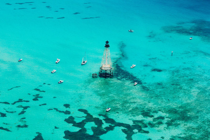 High angle view of sailboats and built structure in sea