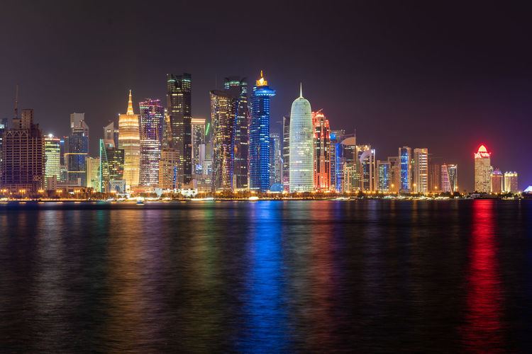 Doha, Qatar Building Exterior Architecture Built Structure Water Waterfront Office Building Exterior Night Illuminated City Landscape Skyscraper Urban Skyline Building Reflection Downtown District Sky Cityscape Travel Destinations Tall - High Modern No People Outdoors Financial District  Doha Qatar Middle East